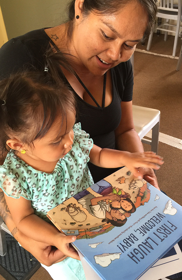 At the Tuba City Library, a visitor at the book launch reads First Laugh to her daughter.