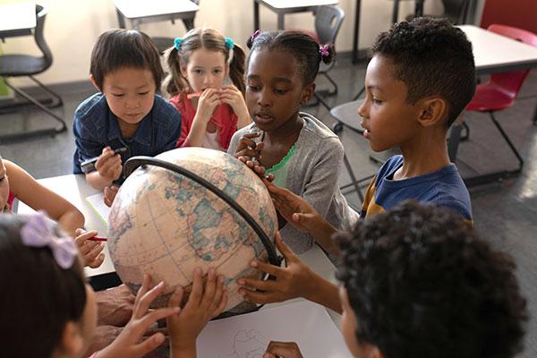 Students examining a globe